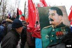 Участники демонстрации Коммунистической партии несут портрет Сталина. Москва, 23 февраля 2013 года.