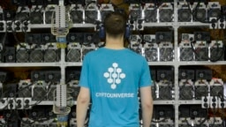 """An employee inspects machines for the production of bitcoins at the CryptoUniverse mining center in Kirishi, Russia. To """"mine"""" cryptocurrencies like bitcoin, you need powerful computers and cheap electricity. (file photo)"""
