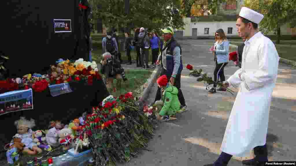 Рядом с учебным заведением установили импровизированный мемориал – черное полотно с фотографиями свечей и надписью «скорбим»