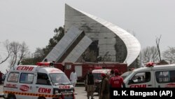 Ambulances and fire brigade arrive near the site of a plane crash in Islamabad on March 11.