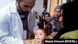طبيب يعالج اطفال اسر نازحة