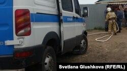 Полицейский микроавтобус на фоне сотрудника службы пожаротушения.