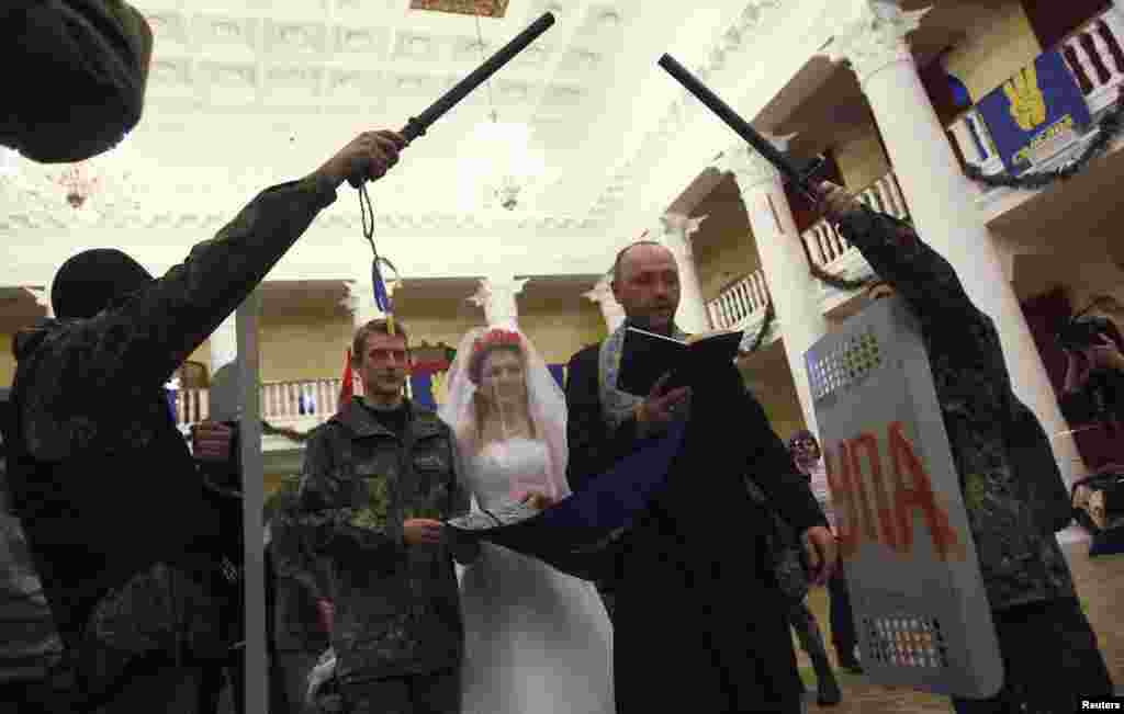 Ukrainian antigovernment protesters Bogdan (second left), 21, and Yulia, 25, hold their wedding ceremony in a city municipality building occupied by protesters in Kyiv on February 5. (Reuters/David Mdzinarishvili)