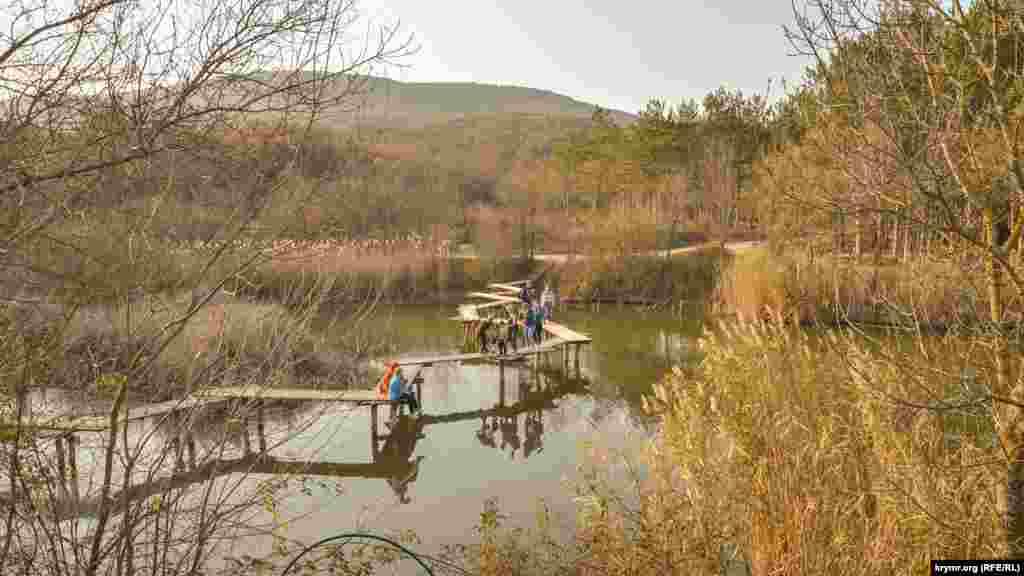 Этот витой мостик через озеро на Севастопольской Тороповой даче соединяет два его берега. Отдыхающие любят не только ходить по мостику, но и просто сидеть на нем прямо посреди озера