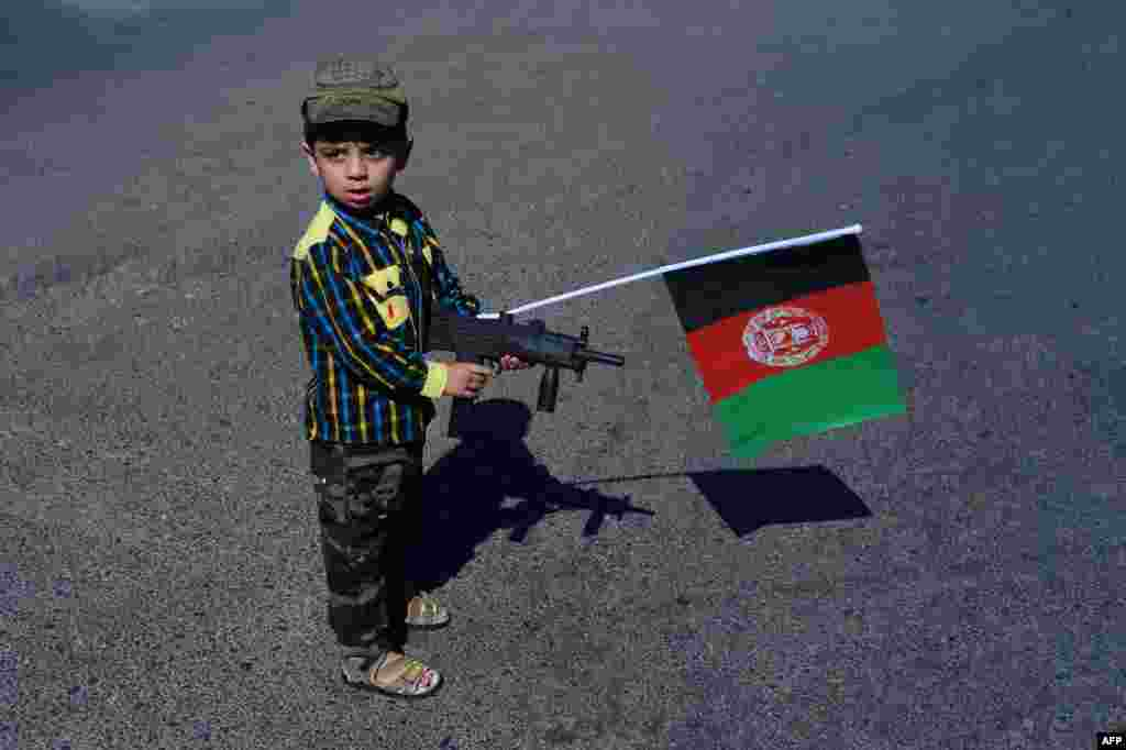 An Afghan boy holds a toy gun as he attends an anti-Pakistan demonstration in Herat after clashes between forces on the border between Afghanistan and Pakistan. (AFP/Aref Karimi)
