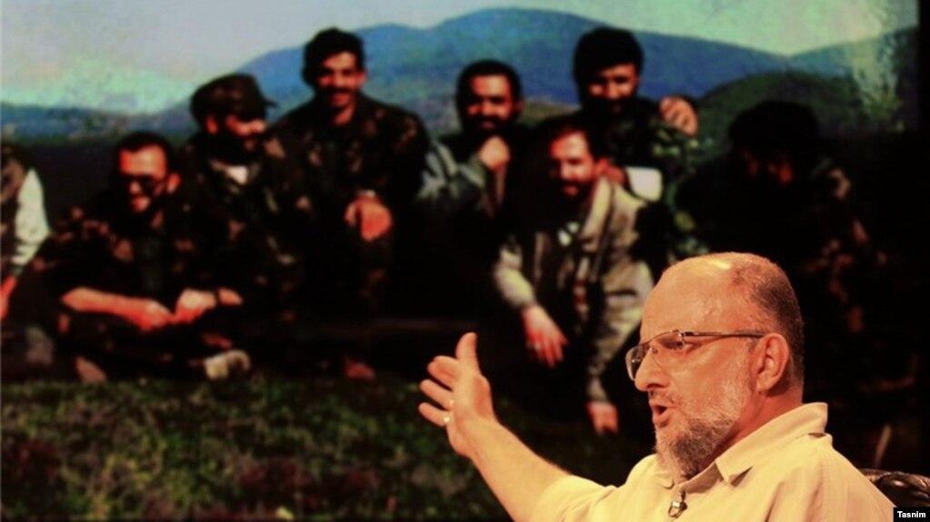 سعید قاسمی با تصویری در پسزمینه که او را در جریان حضور در جنگ بوسنی نشان میدهد.