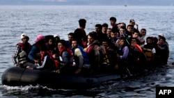 Мигранты и беженцы в надувной лодке у берегов греческого острова Лесбос, 9 сентября 2015 года.
