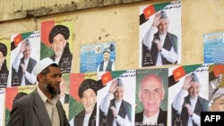 A man walks past posters of presidential candidates on a wall in Kabul.