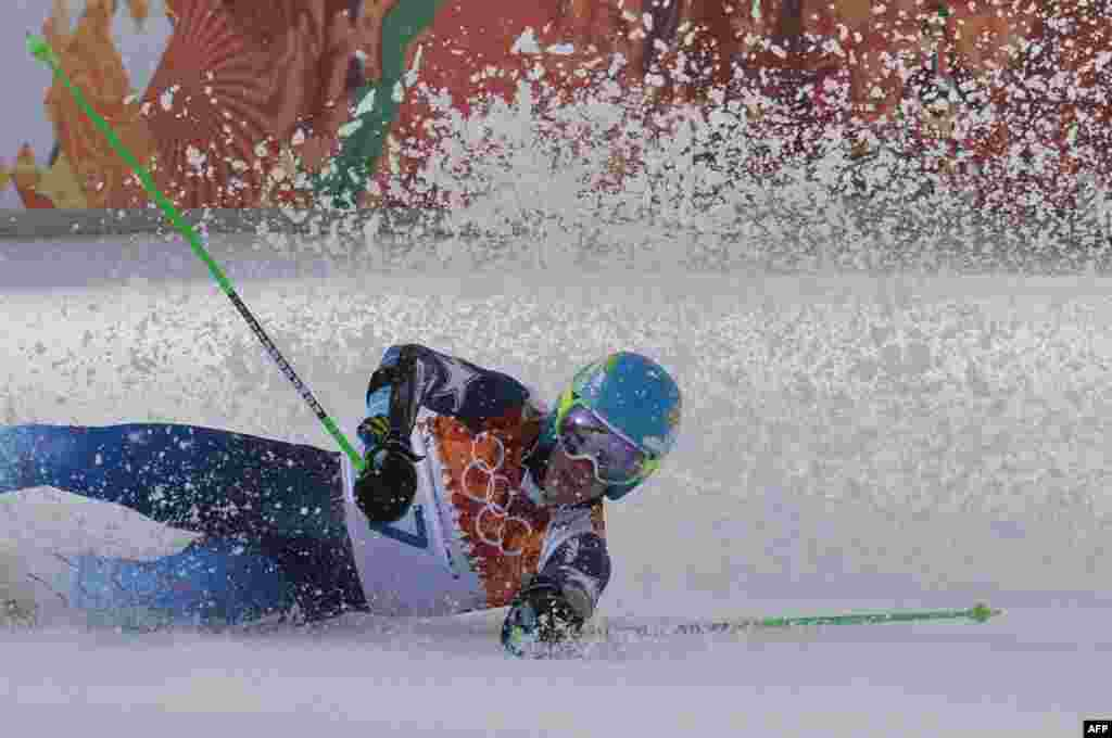 In the same competition, U.S. skier Ted Ligety falls in the finish area after taking gold. He also won a skiing gold at the 2006 Olympics. (AFP/Dimitar Dilkoff)