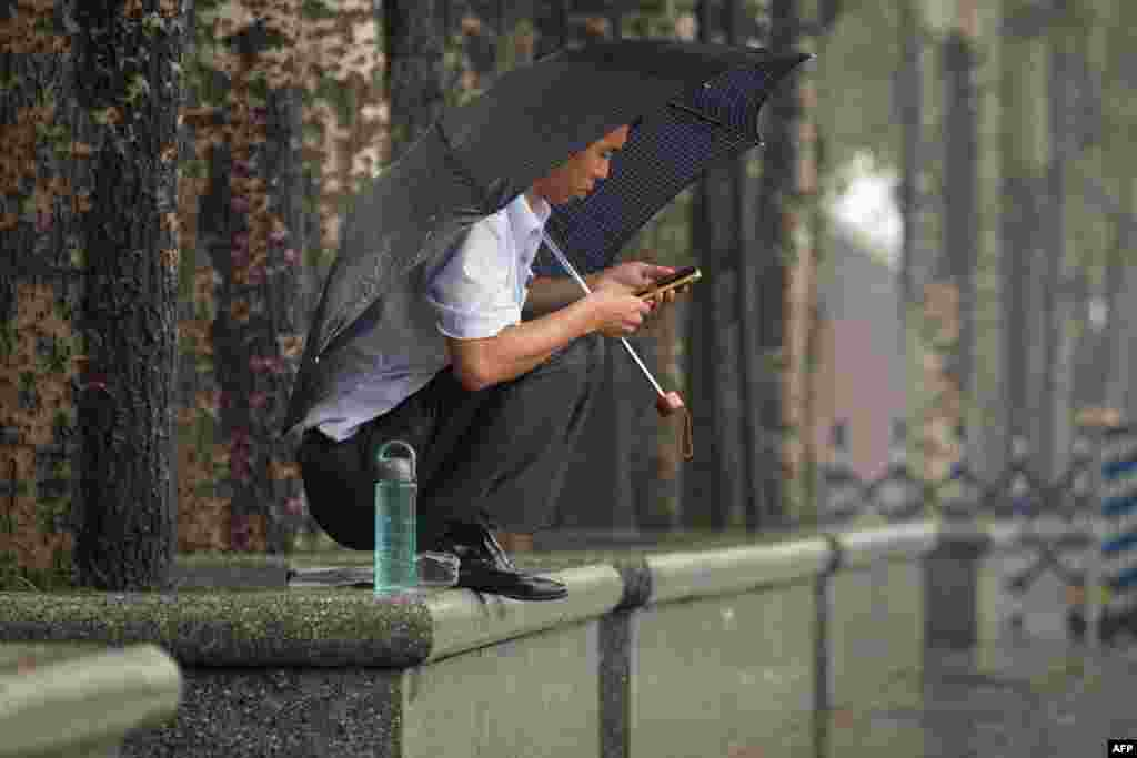 A man shelters beneath an umbrella during rainfall in Beijing.