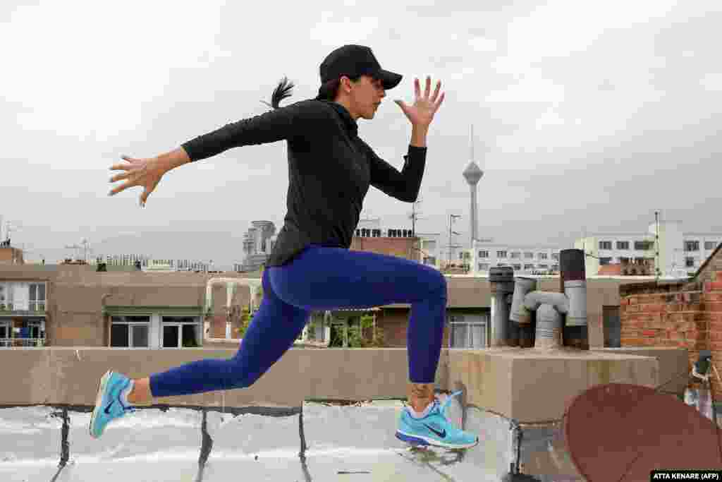 Iranian athlete Maryam Toosi practices on the rooftop of her apartment building following the closure of sports facilities as part of measures aimed at containing the coronavirus in Tehran. (AFP/Atta Kenare)
