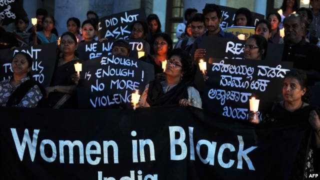 Indian activists belonging to various rights organizations hold placards and candles while they stage a demonstration in Bangalore condemning the recent gang-rape case.