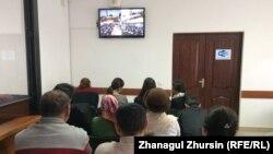 Журналисты в зале, где установлен монитор, по которому транслируют происходящее в зале судебных заседаний. Актобе, 5 декабря 2017 года.