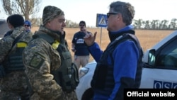 Ukrainian soldiers talk with monitors of the OSCE Special Monitoring Mission in Donbas in October 2015.