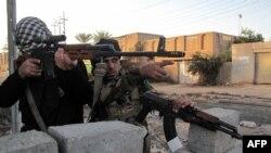 جندي ومقاتل عشائري يتخذان موقعاً خلال اشتباك مع مسلحي داعش في الرمادي