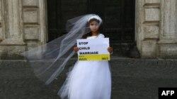 """Një vajzë duke mbajtur mbishkrimin """"Ndalni martesat e fëmijëve""""."""