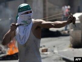 Palestinac gađa izraelsku policiju iz praćke u nemirima u Istočnom Jeruzalemu 25. aprila