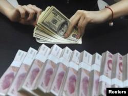 Доллар санап отырған қытай банкінің қызметкері. Хэйфей, 21 қыркүйек 2010 ж.