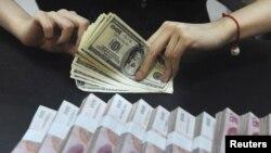 Қытай банк қызметкері юань мен долларды санап отыр. Хефэй, Қытай, 21 қыркүйек 2010 жыл.