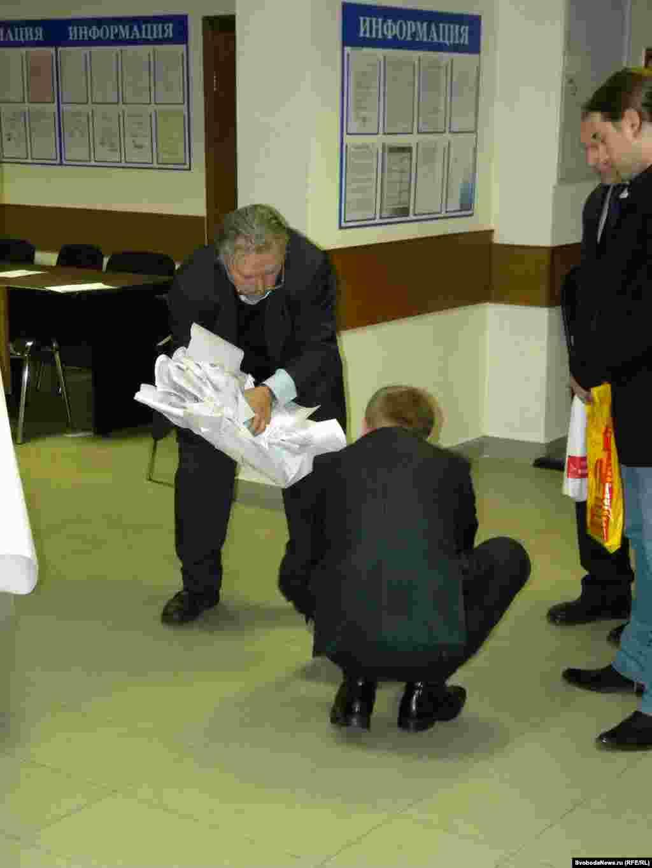 Бюллетени высыпались, и люди, чертыхаясь, бросились их собирать. Человек с бюллетенями в руках - председатель УИК Борис Солоницын