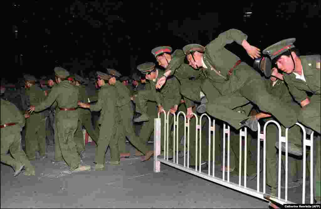 People Liberation Army (PLA) soldiers leap over a barrier on Tiananmen Square in central Beijing during heavy clashes with people and dissident students on June 4, 1989.