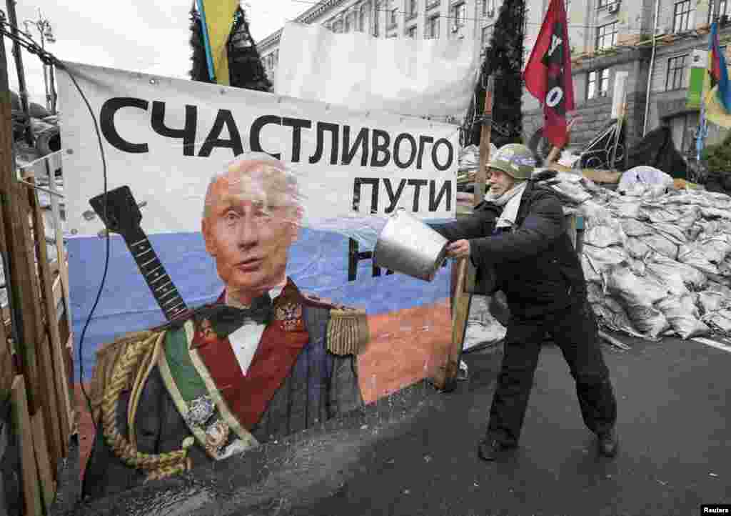 A pro-European-integration demonstrator washes a banner with an image of Russian President Vladimir Putin near a barricade on Independence Square, where the supporters are holding a rally, in Kyiv. (Reuters/Gleb Garanich)