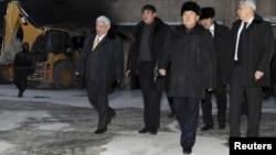 Президент Казахстана Нурсултан Назарбаев с чиновниками проходит мимо сгоревшего здания. Жанаозен, 22 декабря 2011 года.