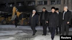 """Қазақстан президенті Нұрсұлтан Назарбаев (алдыда), оның артында - күзеті мен """"ҚазМұнайГаз"""" компаниясының басшысы Ләззат Қиынов. Жаңаөзен, 22 желтоқсан 2011 ж."""