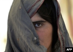 An Afghan refugee, recently returned from Pakistan, waits at a UNHCR center in Jalalabad. Tens of thousands of Afghan refugees have returned, with many claiming to have been beaten by police, detained, and evicted from their homes in Pakistan.