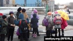 Ученики школы-лицея № 46 города Шымкента в ожидании автобуса, который доставит их в другую школу, поскольку в их учебном заведении не завершен ремонт. 24 ноября 2014 года.
