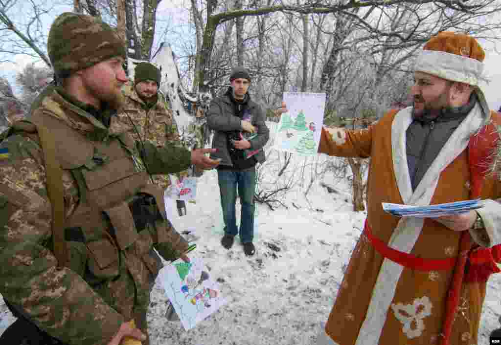 Волонтер, одягнений в костюм Святого Миколая, дарує військовим малюнки дітей. Передові позиції українских військових біля Волновахи, Донецька область, 28 грудня 2016 року