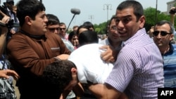 Plainclothes Azerbaijani police officers on May 23 detain the opposition activists who tried to hold a rally near the public television station that is showing the Eurovision broadcasts in Baku.