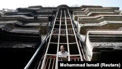 An Afghan man looks out from a damaged building after the July 28 attack in Kabul.