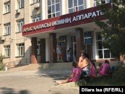Арыс қаласы әкімдігі алдында отырған адамдар. Түркістан облысы, 1 тамыз 2019 жыл.