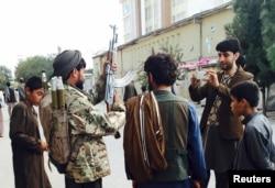 Taliban döyüşçüsü (soldan ikinci) Talibanın Kunduz şəhərinin ələ keçirməsindən sonra. 29 sentyabr 2015