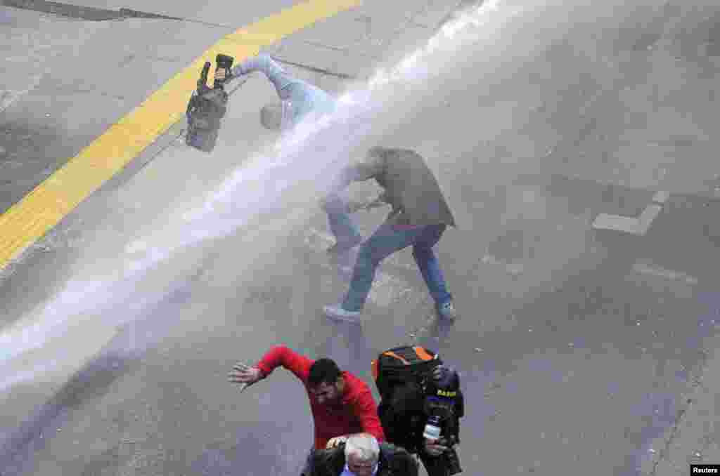 Media personnel run as riot police use water cannon to disperse protesters outside the Supreme Electoral Council in Ankara on April 1. (Reuters)