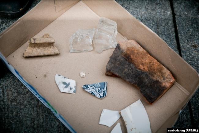 Рэшткі шкляной попельніцы, аскепкі парцалянавага посуду, фрагмэнты кафлі, знойдзеныя падчас раскопак