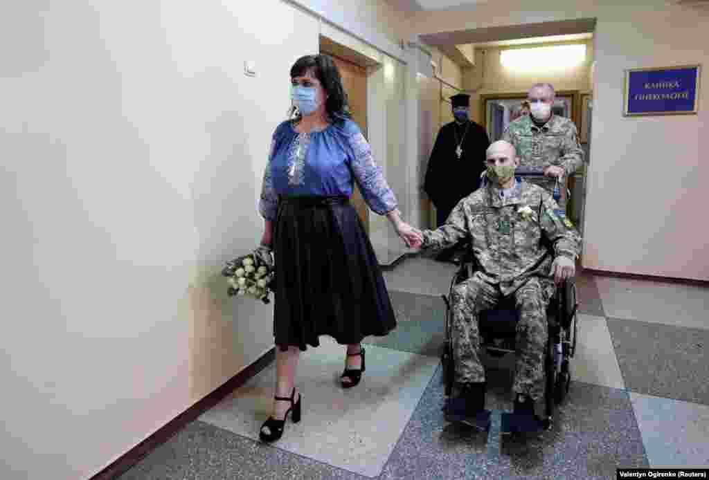 Ihor Ponomarchuk, a Ukrainian serviceman injured in the military conflict in the country's eastern regions, and his bride, Anna Diolomina, arrive for a wedding ceremony at the Main Military Clinical Hospital amid the coronavirus outbreak in Kyiv. (Reuters/Valentyn Ogirenko)