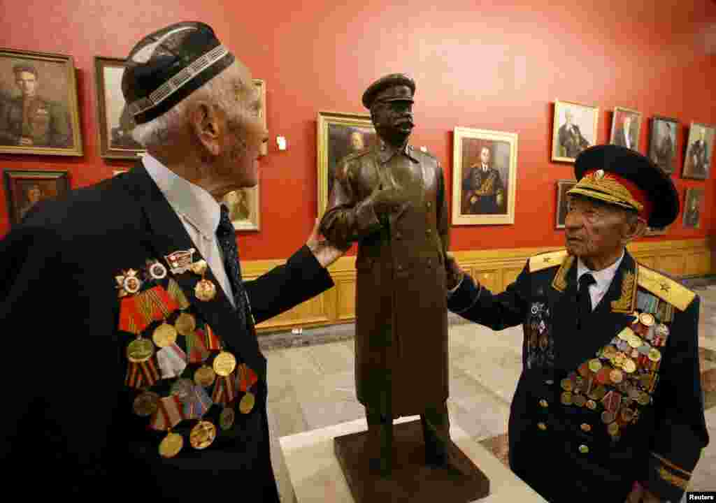 World War II veterans touch an exhibit showing Soviet leader Josef Stalin at the Central Museum of the Great Patriotic War in Moscow on April 28. (Reuters/Sergei Karpukhin)