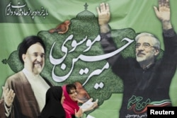 A photo from 2009 showing women walking past a picture of then presidential candidate Mir Hossein Musavi (right) and former President Mohammad Khatami in Tehran.