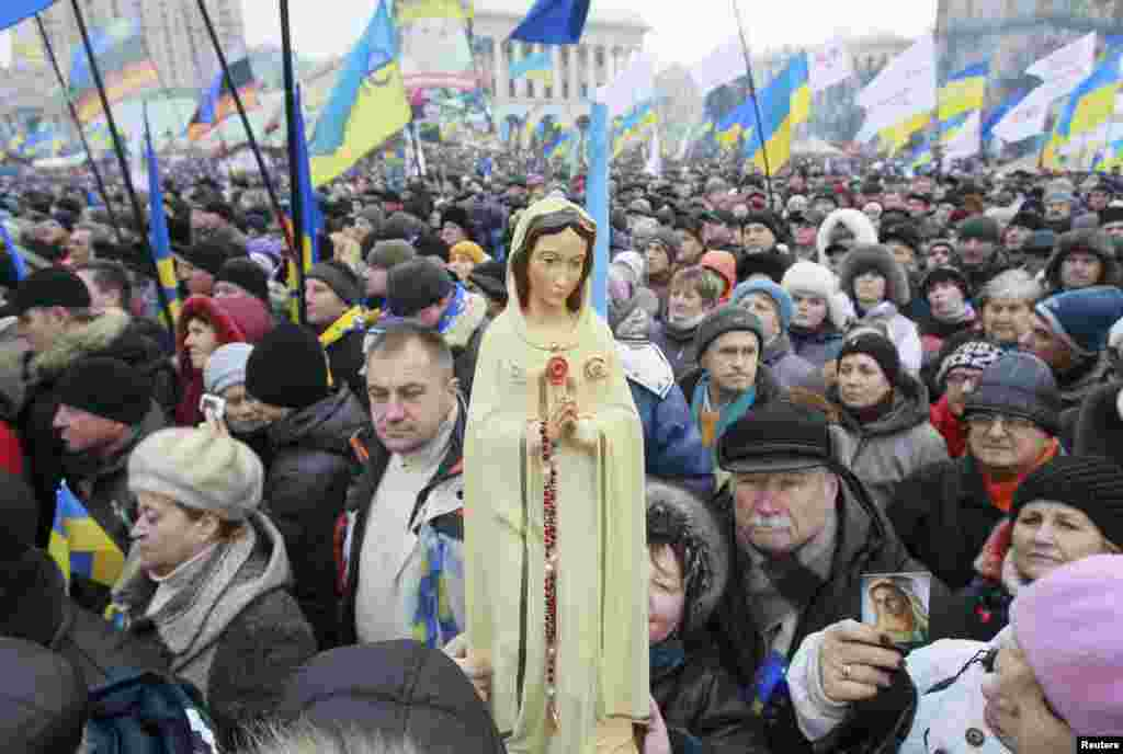 Pro-EU protesters hold up a statue of the Virgin Mary.