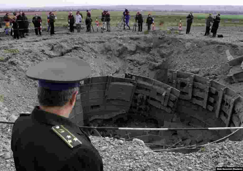 A Ukrainian Army officer inspects a destroyed SS-24 missile silo near the town of Pervomaysk in Ukraine's Mykolayiv region. By the end of 2001, Ukraine had destroyed all of 46 of its intercontinental ballistic missile silos.