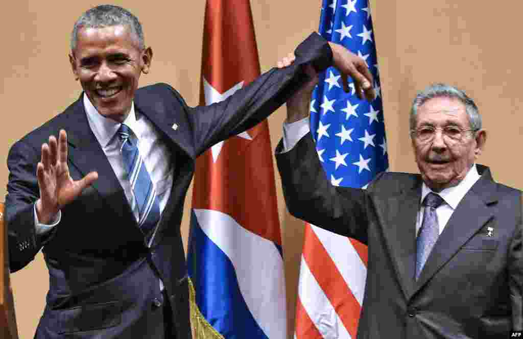 Cuban President Raul Castro raises Obama's hand during a meeting at the Revolution Palace in Havana on March 21, 2016. Obama's visit to Cuba was the first by a U.S. president since the country's 1959 revolution, and marked a historic warming of ties between the two countries.