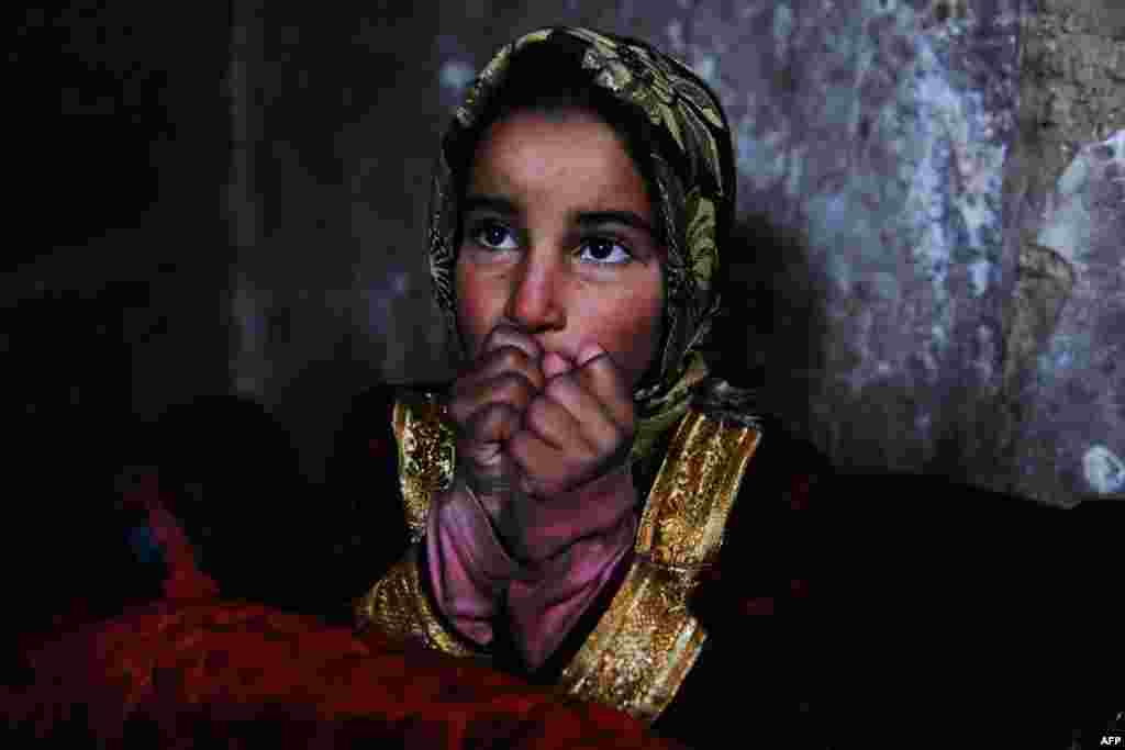"An Afghan child warms herself near a traditional ""sandali"" stove at her family's home in Herat. (AFP/Aref Karimi)"