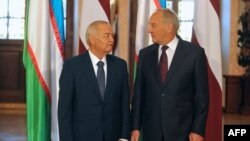 Latvian President Andris Berzins (right) and Uzbek counterpart Islam Karimov pose in front of their national flags as they meet in Riga on October 17.
