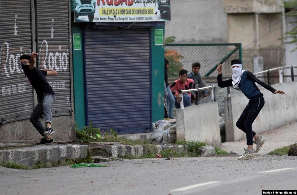 Мужчины бросают камни в сторону индийских полицейских. 10 августа 2019 года. Регион, на который претендуют как Пакистан, так и Индия, является причиной почти всех крупных конфликтов между этими двумя странами.