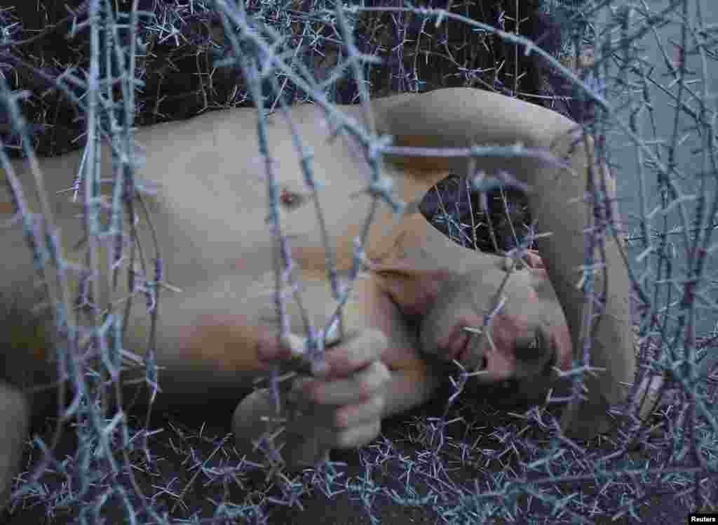 Pavlensky lies on the ground wrapped in barbed wire during a protest action in St. Petersburg in May 2013 to condemn the prosecution of punk collective Pussy Riot.