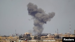 A plume of smoke rises above a building following a U.S. air strike in the Iraqi city of Tikrit in March of this year.