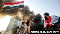 A masked protester flashes the victory gesture as he waves an Iraqi national flag before a burning building during a demonstration against state corruption and poor services on October 1.