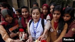 Students light candles as they gather to pray and pay tribute to the victims of the Taliban attack on the Army Public School in Peshawar, Pakistan.